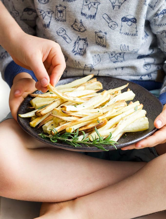 Child Grabbing a Roasted Parsnip from a plate