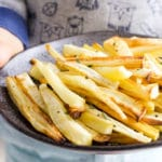 Child Holding a Plate of Roasted Parsnips