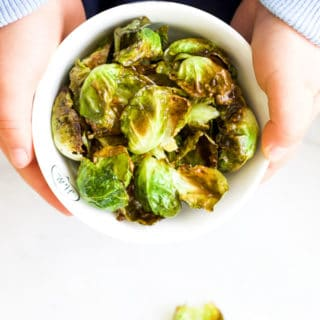 Child Holding Bowl of Brussels Sprouts Chips