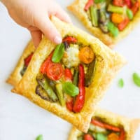 Child Holding a Puff Pastry Tart Filled with Roasted Vegetables
