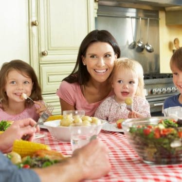 Family with Young Children Sitting at Table for Family Meal