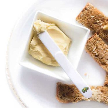 Dish of Homemade Butter with Kid's Knife and Toast Fingers
