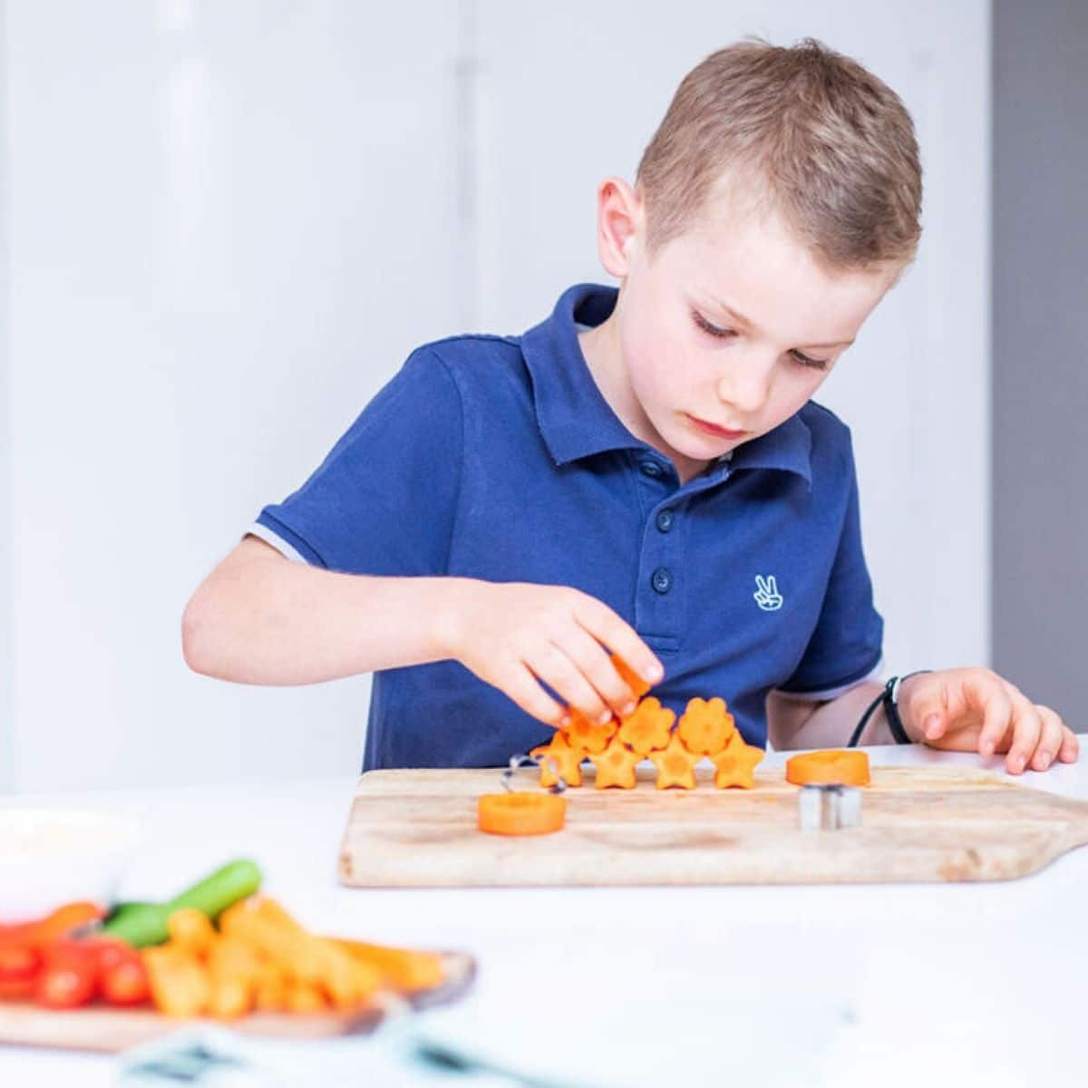 Child Stacking Carrots Cut in Different Shapes