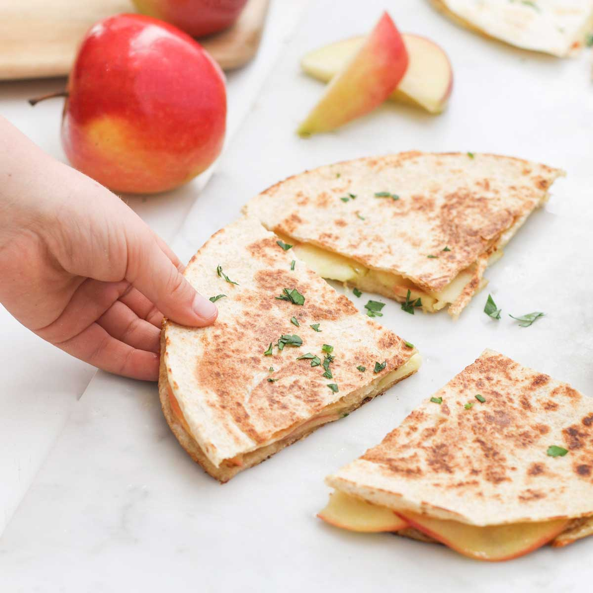 Child Grabbing Apple and Cheese Quesadilla