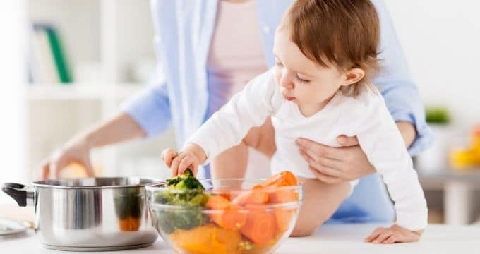 Baby Touching Food in Kitchen