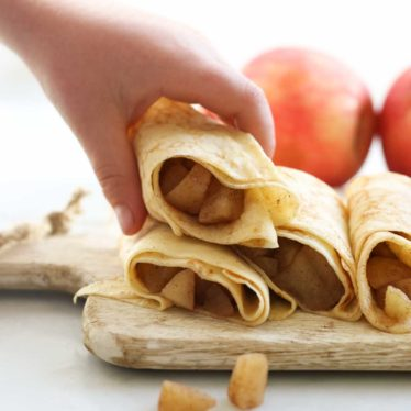 Child Grabbing a Filled Apple Crepe from Stack