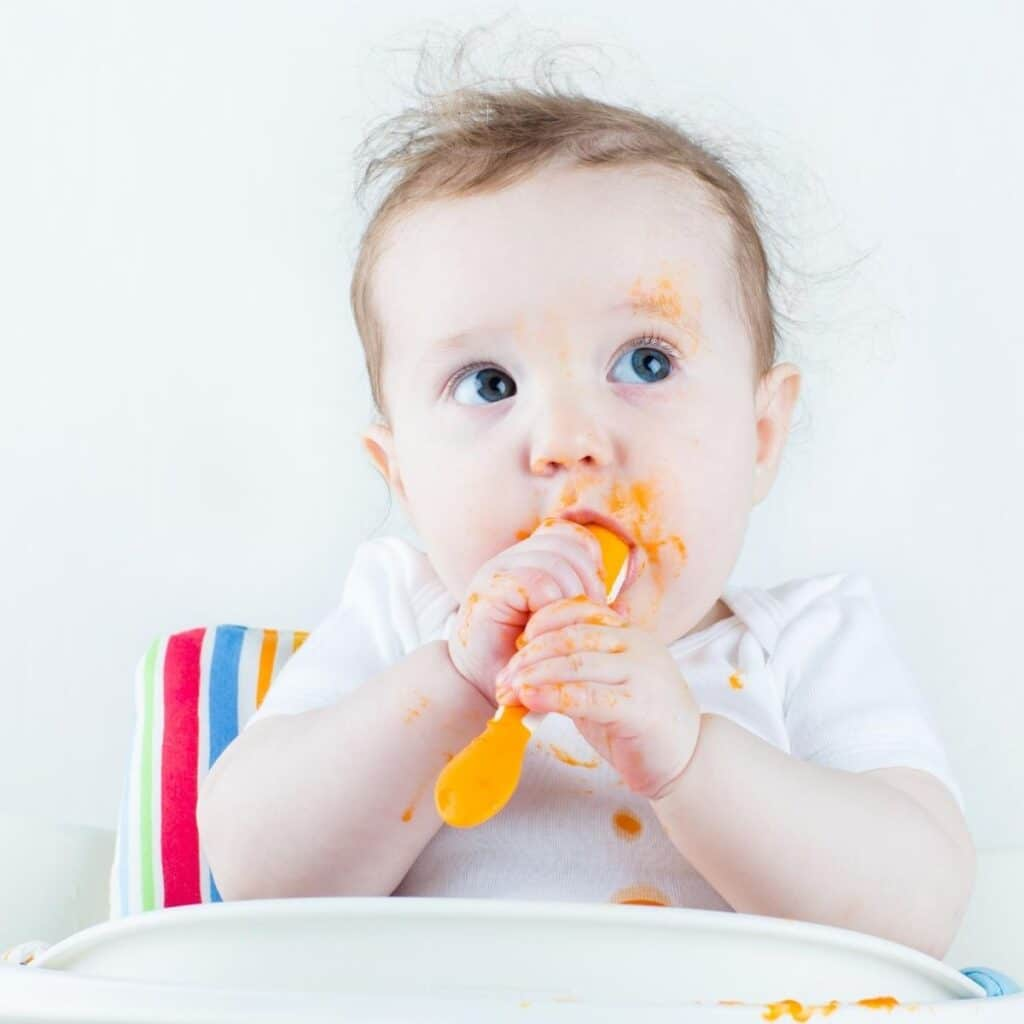 Baby in Highchair Chewing Spoon