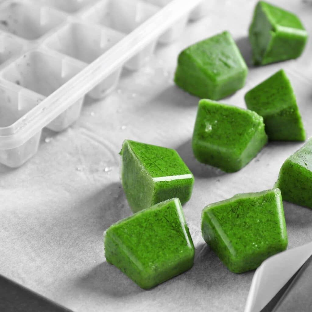 Frozen Cubes of Green Baby Puree Next to IceCube Tray