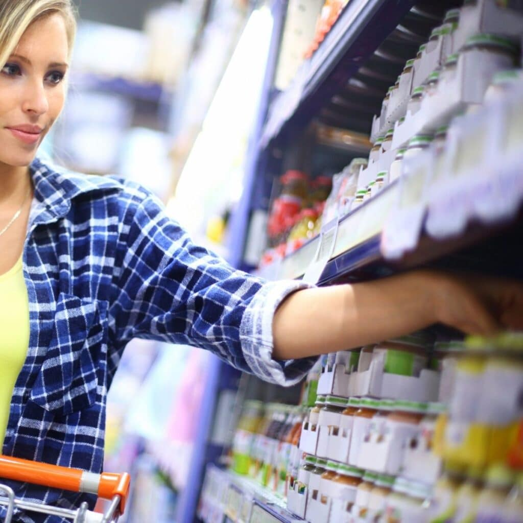 Women Looking at Jars of Baby Food on Supermarket Shelves