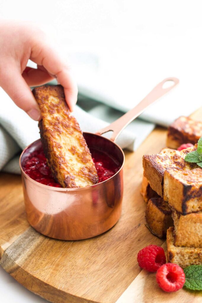 Child Dipping Eggy Bread Stick into Fruit Compote