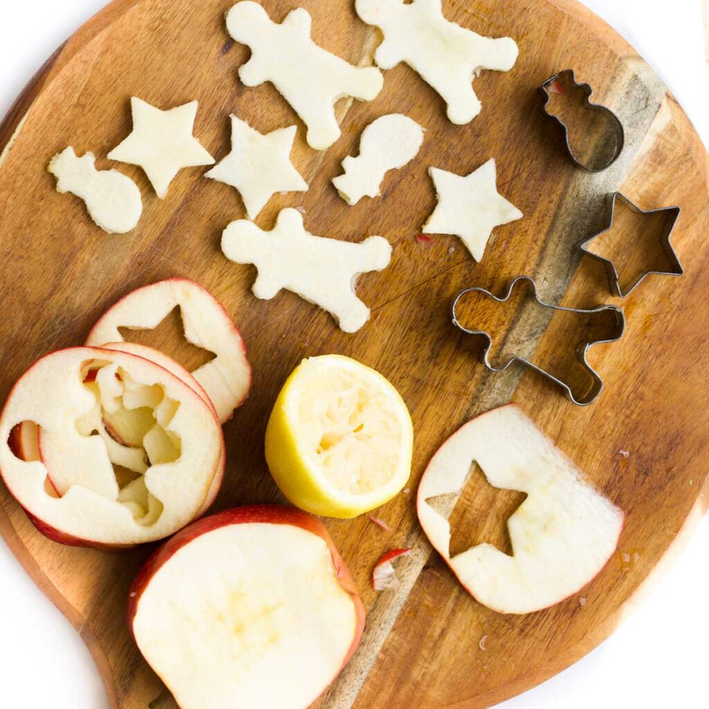 Chopping Board with Slices of Apple (with cookie cutter shapes cut out) and Lemon