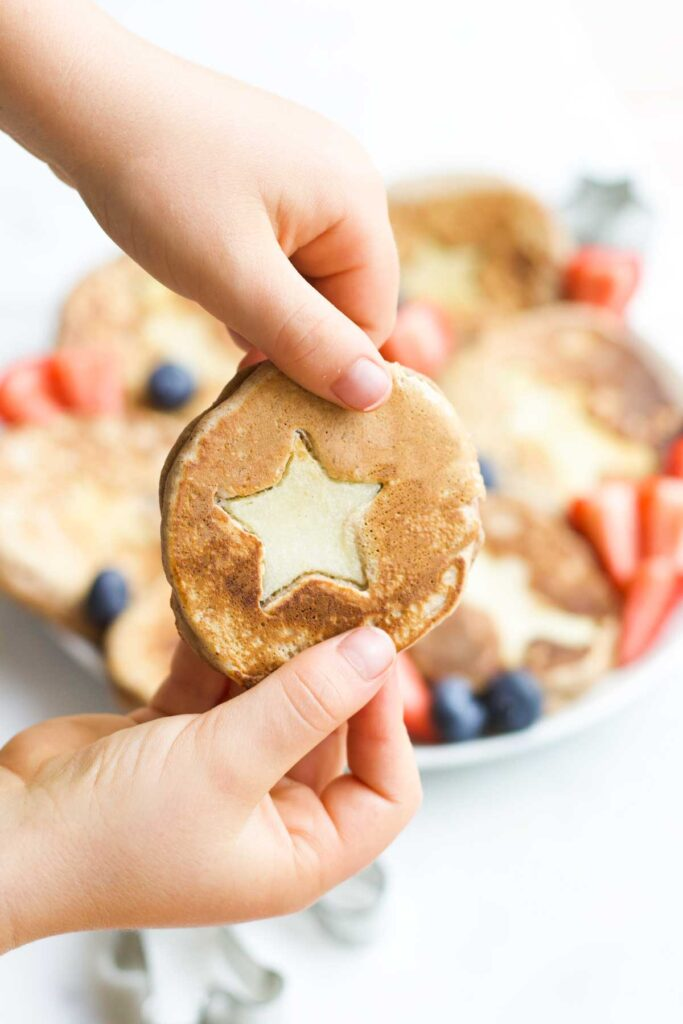 Child Holding Christmas Spiced Pancake with Star Apple Insert