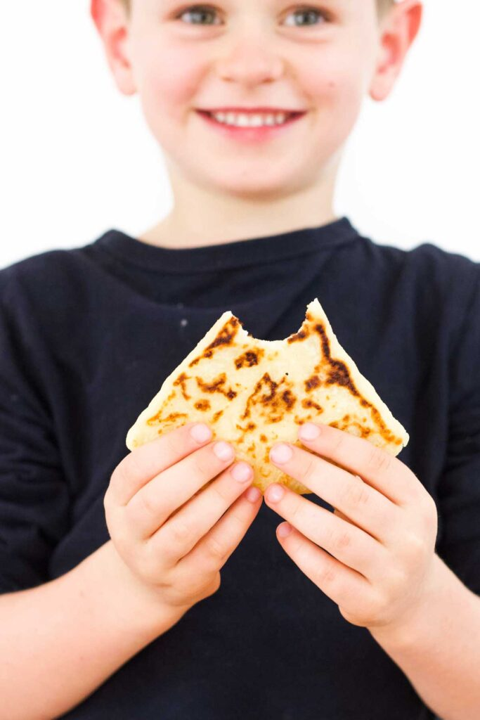 Child Holding Tattie Scone with Bite Taken Out