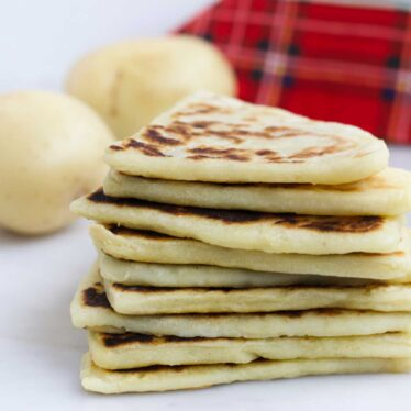 Stack of Tattie Scones with Potatoes adn Tartan Napkin in Background
