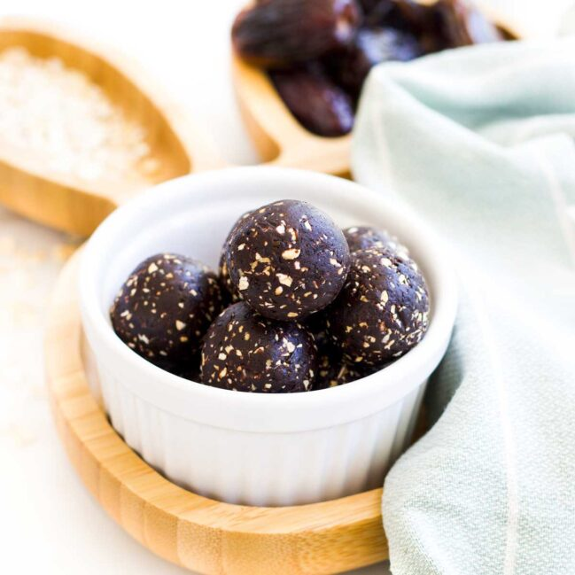 45 Degree Shot of cocoa Balls in White Bowl Sitting on Wooden Bunny Plate