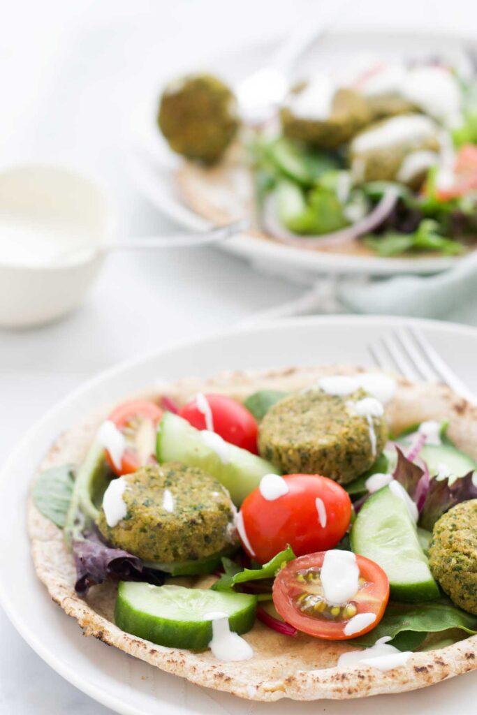 Two Plates of Falafel on Pita Bread with Salad and Yogurt Dressing