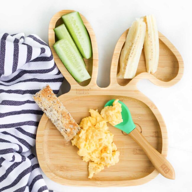 Top Down View of Scrambled Eggs on Baby Plate with Toast Finger, Cucumber and Banana