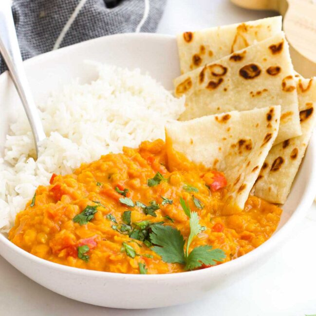 Bowl of Red Lentil Curry with Rice and Roti Bread