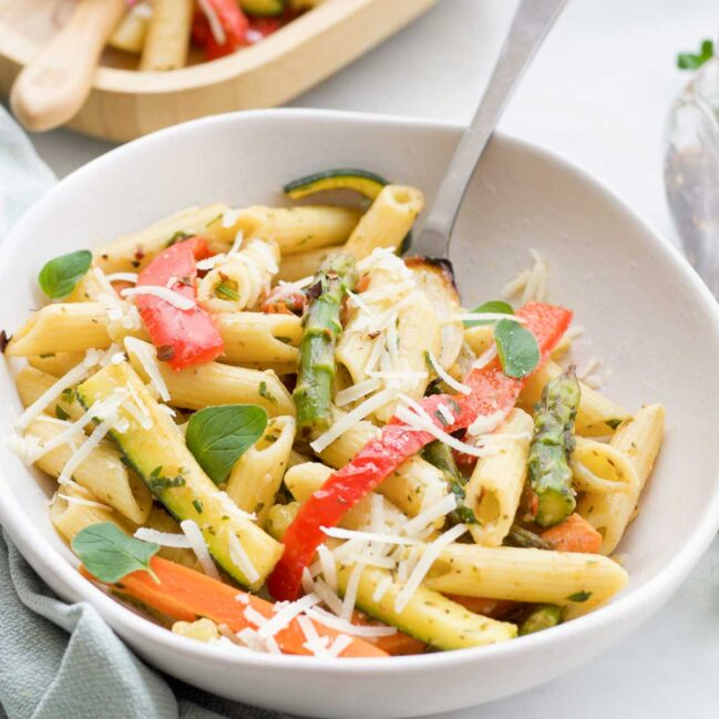 Bowl of Penne Pasta and Roasted Vegetables Scattered with Parmesan Cheese