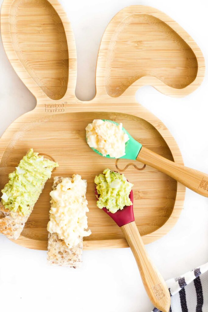 Baby Plate with Mashed Egg and Avocado on a Spoon and Spread on a Toast Finger.