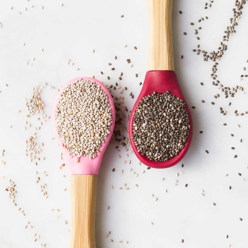 Top Down View of Two Spoons One with White Chia Seeds and One With Black Seeds