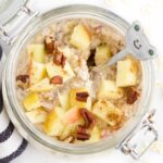 Overhead Shot Of Apple Overnight Oats in Mason Jar Topped with Apple Pieces and Pecan Nuts