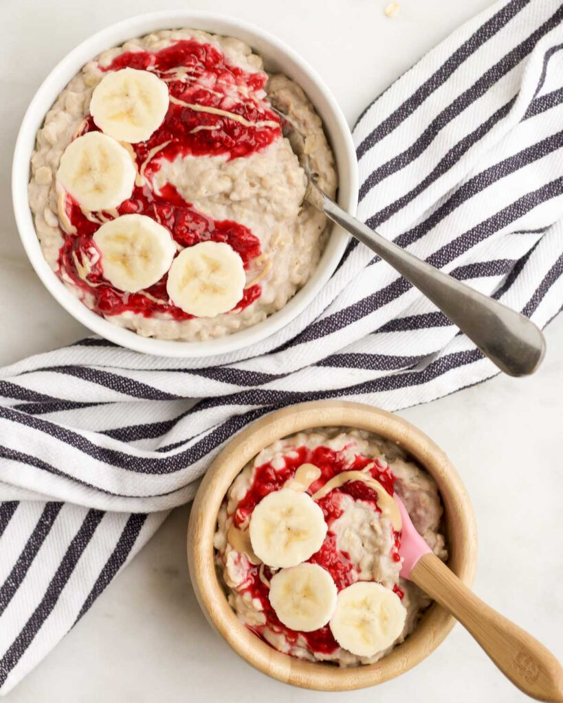 Adult and Toddler Bowl of Banana Porridge Topped with Crushed Raspberries and Banana Slices