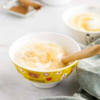 Side Shot of Two Bowls of Apple Yogurt with Cinnamon on Dish in Background