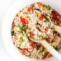 Top Down Shot of Tuna Rice Salad in Large White Bowl with Wooden Salad Spoons.