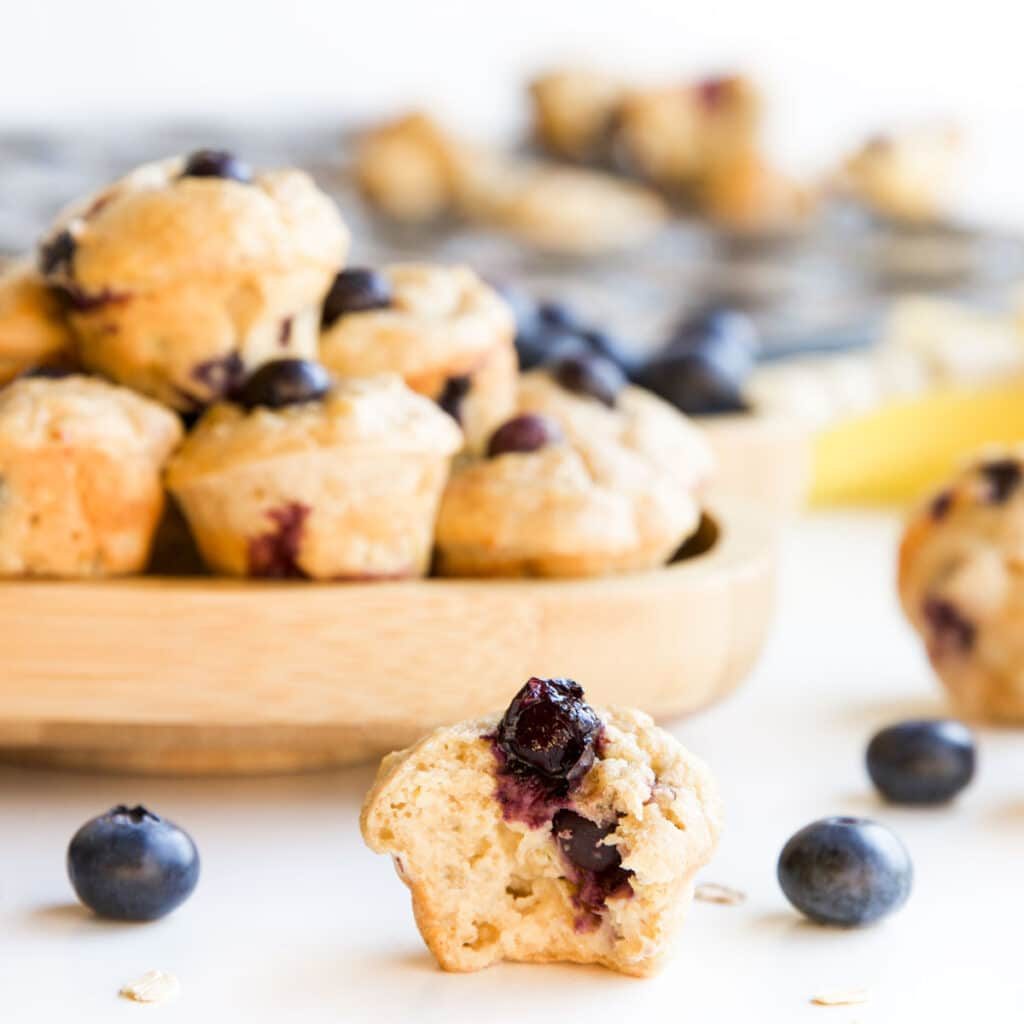 Side on Shot of Mini Blueberry Muffin with Bite Removed. A Plate of Muffing in Background and Muffin Tray