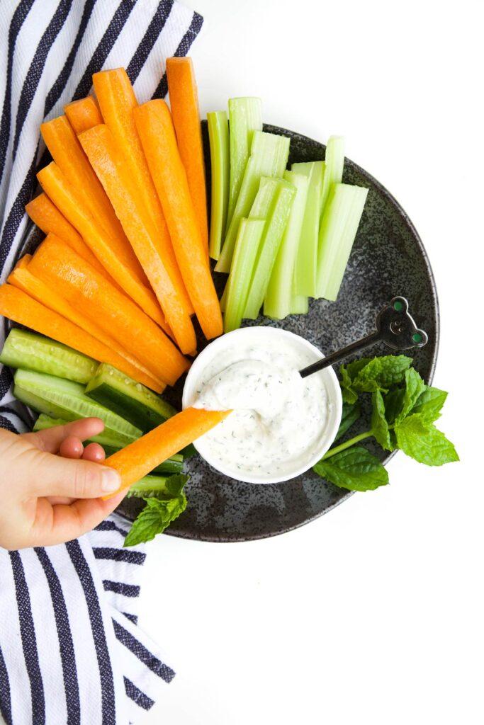 Child Dipping a Carrot Stick into Bowl of Mint Yogurt Dip