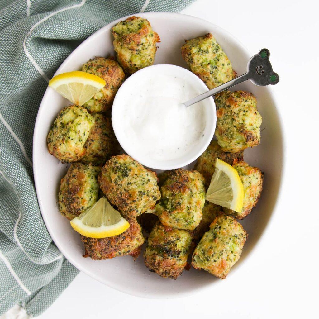 Broccoli Tots in White Bowl with Lemon Yogurt Dip and slices of Lemon