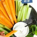 "Child Dipping Carrot in Mint Yogurt Dip with Text Overlay ""Mint Yogurt Dip"""