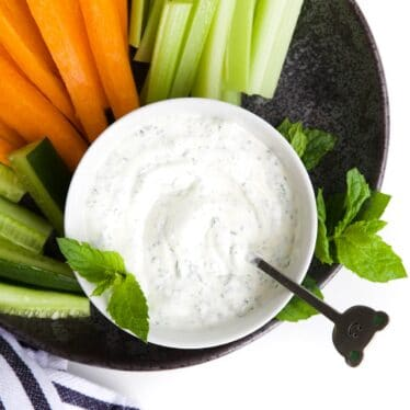 MInt Yogurt Sauce in Bowl Sitting on Plate with Cut Vegetable Sticks