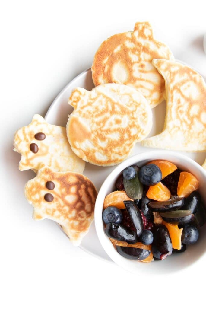 Plate of Halloween Shaped Pancakes (Ghost, Pumpkin, Hat) and Side of Fruit Salad