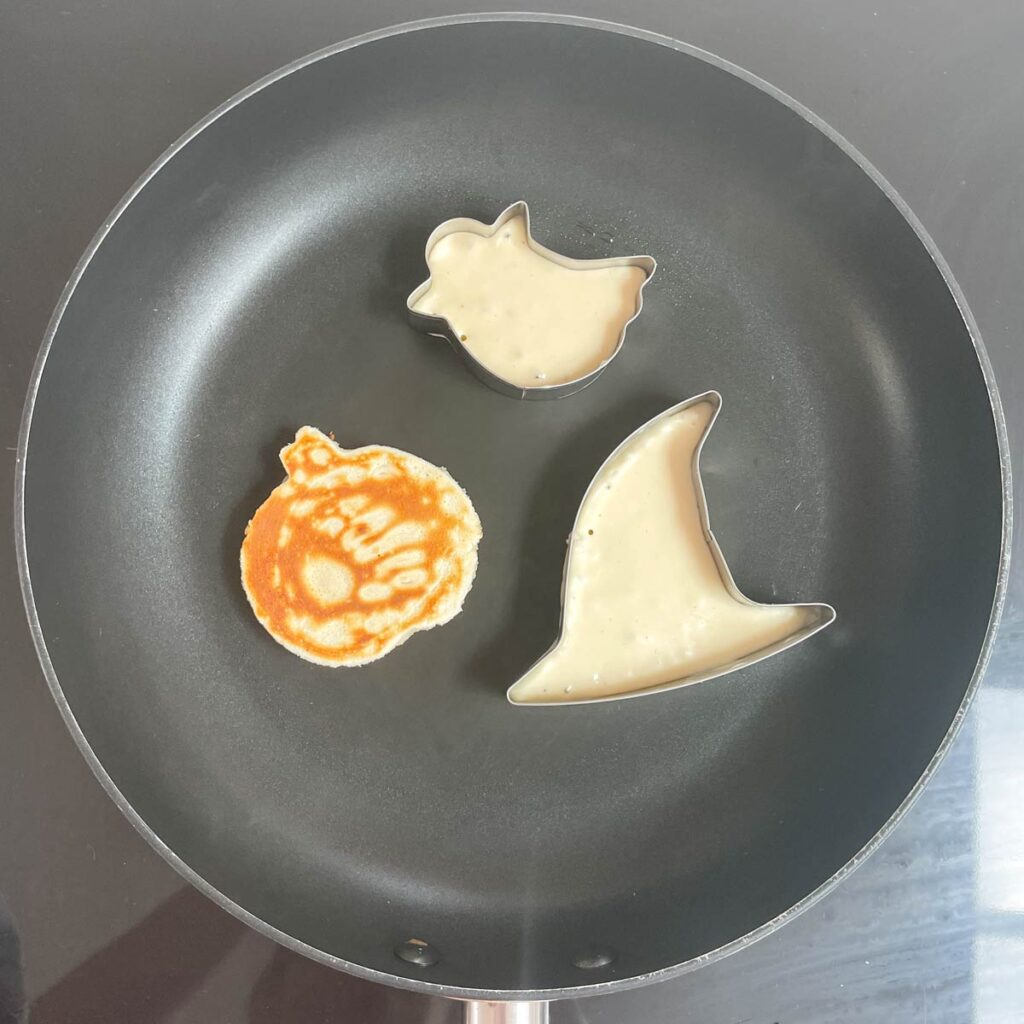 Metal Halloween Cookie Cutters in Pan filled with Pancake Batter