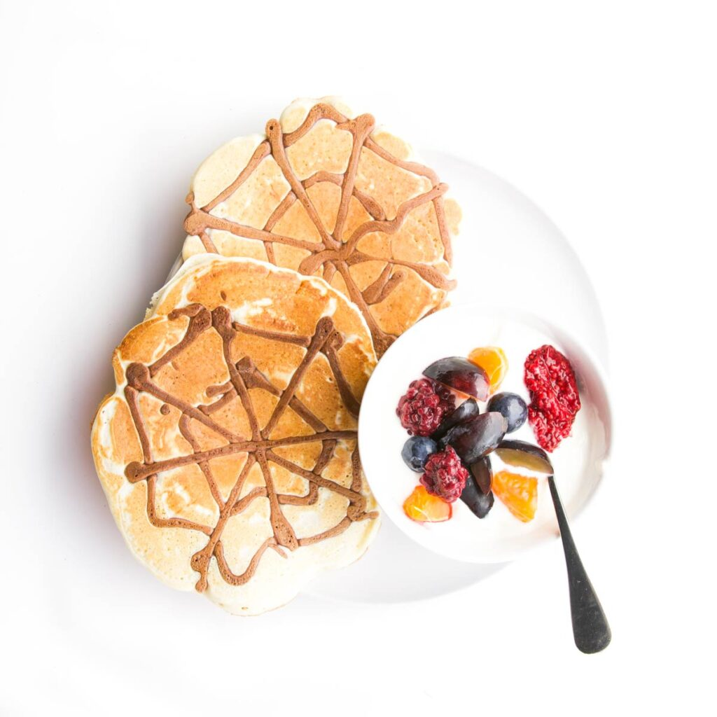 Plate of 2 Spider Web Pancakes with a Side of Yogurt and Fruit